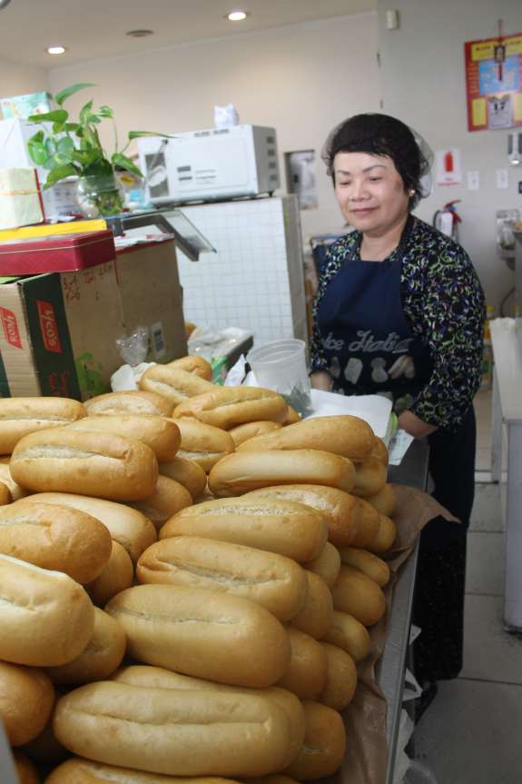 Yen Nguyen stands behind the counter of her Bahn Mi shop Nha Trang Subs.