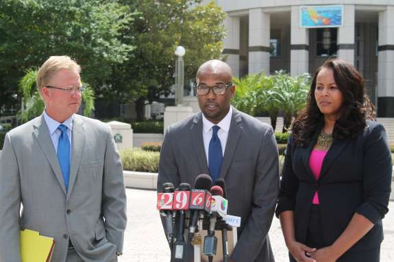 Photo: Attorney Patrick Lawlor; Noel Carter; Attorney Natalie Jackson speak at a press conference in front of the Orange County courthouse.