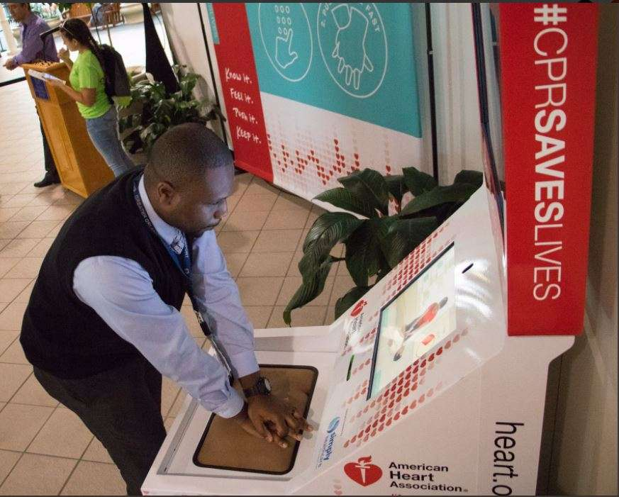 An airport employee uses the hands-only CPR kiosk at Orlando International Airport. Photo: Orlando International Airport.