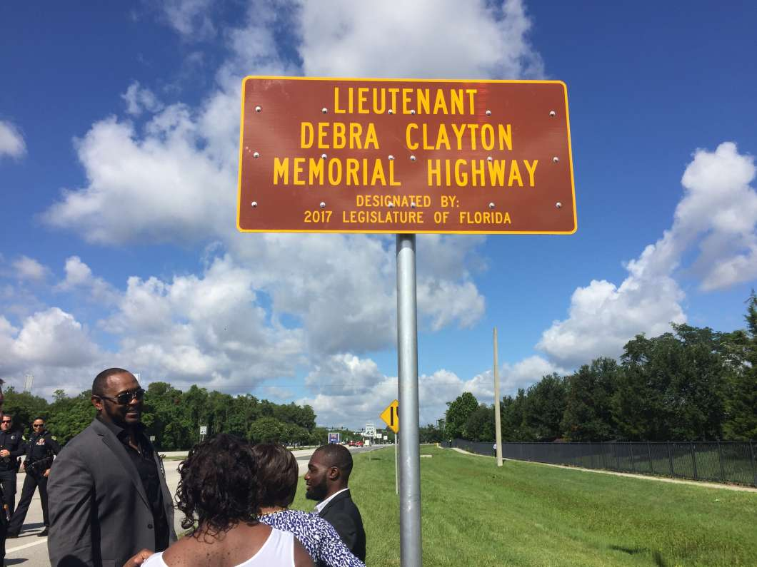 Relatives gather by sign dedicated to Orlando police Lt. Debra Clayton was killed in January 2017 in the line of duty. Photo: Renata Sago.