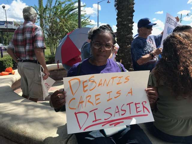Protesters outside a Ron DeSantis campaign stop hold signs calling on healthcare coverage for all. Photo: Danielle Prieur