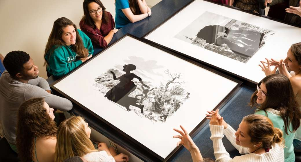 Students discuss the work of Kara Walker during class at the Cornell Fine Arts Museum, Rollins College. Photo: Scott Cook. Kara Walker, Exodus of Confederates from Atlanta from Harper's Pictorial History of the Civil War (Annotated), (detail), 2005, Offset lithography and silkscreen, 39 x 53 in., The Alfond Collection of Contemporary Art, Gift of Barbara R'68 and Theodore R'68 Alfond © 2014 Kara Walker Cornell Fine Arts Museum. Photo: Scott Cook