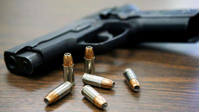 A gun with six bullets on a table