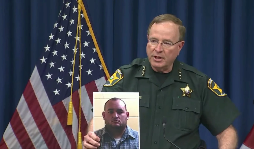 Polk Sheriff Grady Judd holds a mug shot of Deputy Peter Heneen via Facebook Live