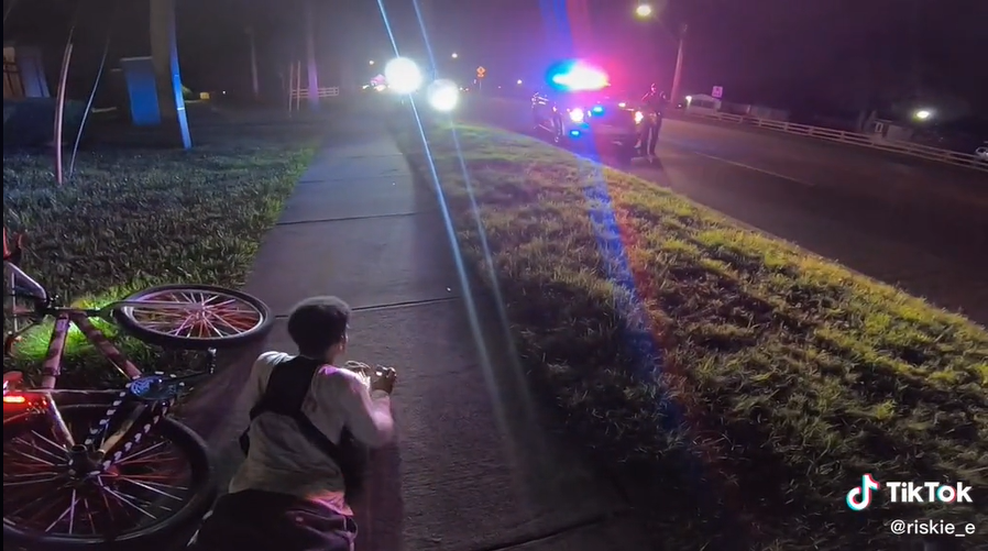 As captured by Ian Adams' GoPro camera Monday night by I-Drive, a screenshot of the viral TikTok video showing Jonathan Medina, 21, complying with Orlando Police orders to get on ground. The officers had guns drawn on the two men, mistaking them for armed robbery suspects.