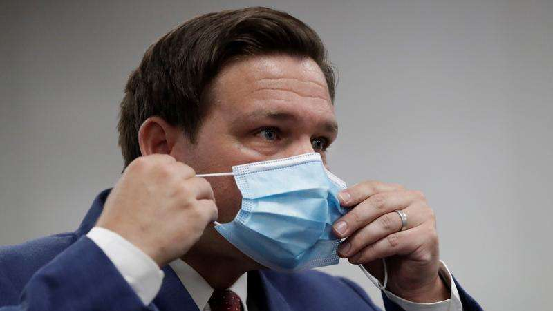 Florida Gov. Ron DeSantis puts on his mask as he leaves a news conference at Jackson Memorial Hospital, Monday, July 13, 2020, in Miami. DeSantis acknowledged Monday that the new coronavirus is spreading and urged people to take precautions such as wearing masks in public places, social distancing and avoiding crowds. (AP Photo/Wilfredo Lee)