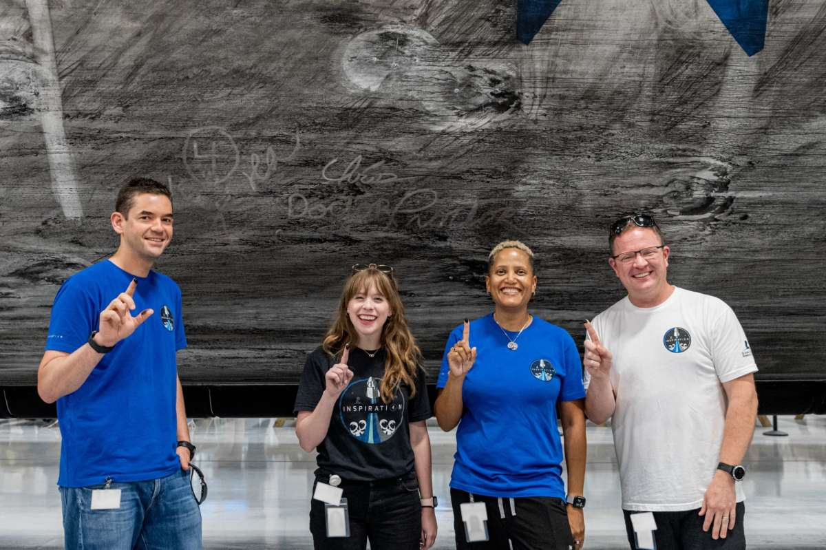The crew of Inspiration4 signs the soot in the Falcon 9 rocket booster that will launch them into space. Photo: Inspiration4 / John Kraus