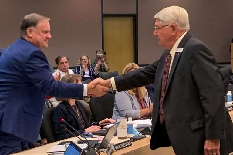 The St. Johns River Water Management District Governing Board appointed Mike Register (left) as Executive Director. Here he is congratulated by Governing Board Chairman Gen. Douglas Burnett. Photo courtesy the St. Johns River Water Management District